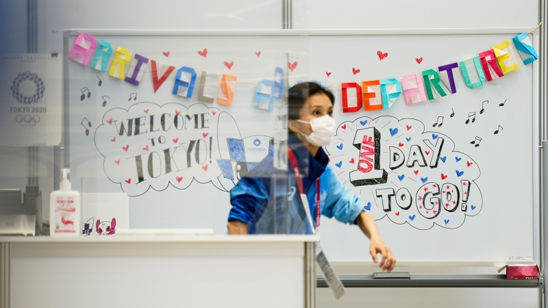 A help desk officer stands behind a plastic barrier due to COVID-19 protocols in the Main Press Center at the 2020 Summer Olympics, Thursday, July 22, 2021, in Tokyo, Japan. (AP Photo/John Minchillo)
