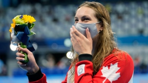 Canada's Penny Oleksiak waves her flowers after winning the bronze medal in the women's 200-metre freestyle final at the 2020 Summer Olympics, July 28, 2021, in Tokyo, Japan. (AP Photo/Martin Meissner)