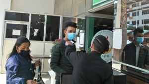 A security official takes the temperature of people as a precaution against the coronavirus in Thimpu, Bhutan, Monday, April 12, 2021. The tiny Himalayan kingdom wedged between India and China has vaccinated nearly 93% of its adult population since March 27. Overall, the country has vaccinated 62% of its 800,000 people. (AP Photo)
