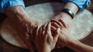 Two people hold hands in this stock image. (Pexels)