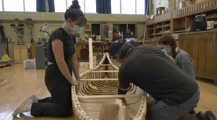 Students work on a canoe as part of traditional learning in the UGDSB