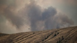 A helicopter flies behind a ridge as the Tremont Creek wildfire burns on the mountains above Ashcroft, B.C., on Friday, July 16, 2021. (Darryl Dyck  / THE CANADIAN PRESS)