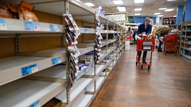 In this Friday, March 13, 2020 file photo, shoppers browse empty shelves at a supermarket in Larchmont, N.Y, amid panic-buying due to the coronavirus outbreak.  (AP Photo/John Minchillo, File)