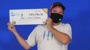 John Lloyd, 45, of Oro-Medonte, Ont., holds his cheque for $243,296.70 after winning a Lotto Max second prize in the July 16, 2021, draw. (OLG)