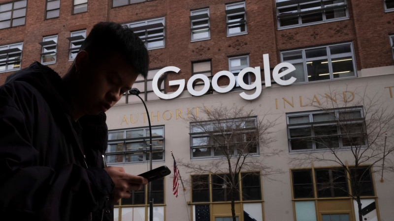In this Dec. 17, 2018, file photo, a man using a mobile phone walks past Google offices in New York. (AP Photo/Mark Lennihan, File)