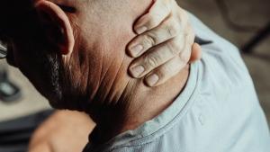 Stock photo of older man holding his neck. (Kendel Media)