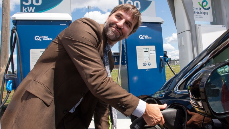 Canadian Heritage Minister Steven Guilbeault plugs in an electric car at a news conference Wednesday, July 28, 2021 in Laval, Quebec. Guilbeault announced the installation of more electric car charging stations across Quebec. THE CANADIAN PRESS/Ryan Remiorz