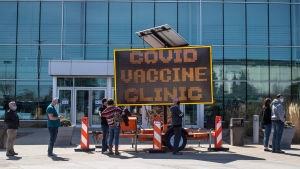 People line up outside an immunization clinic to get their COVID-19 vaccine in Edmonton, Tuesday, April 20, 2021. (THE CANADIAN PRESS/Jason Franson)