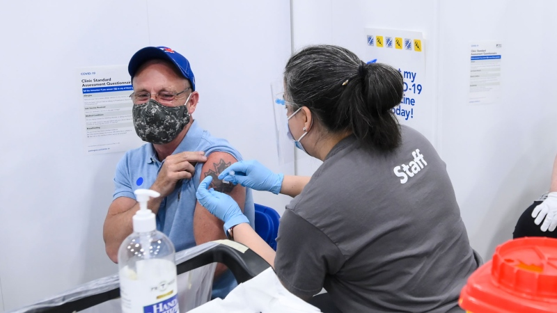 Todd Myles, left, receives his first dose of the COVID-19 vaccine at the 'hockey hub' mass vaccination facility at the CAA Centre during the COVID-19 pandemic in Brampton, Ont., on Friday, June 4, 2021. THE CANADIAN PRESS/Nathan Denette