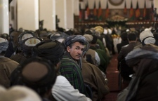 An Afghan man follows Afghanistan President Hamid Karzai's inauguration ceremony at the Presidential Palace in Kabul, Afghanistan, Thursday, Nov. 19, 2009. After being sworn in to a second five-year term, Karzai said his government was doing whatever it could to implement reforms. (AP / Anja Niedringhaus)