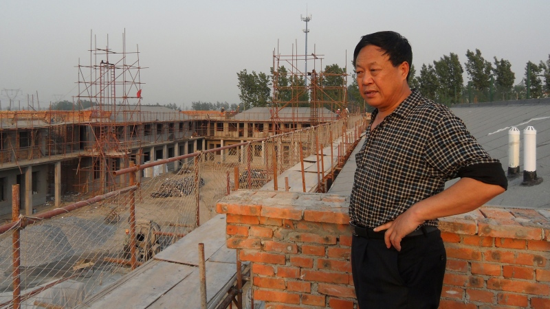 In this May 5, 2012, photo provided by the Legal Team of Dawu Group, Sun Dawu stands at a construction site for Dawu Town in Baoding in northern China's Hebei Province. (Legal Team of Dawu Group via AP)