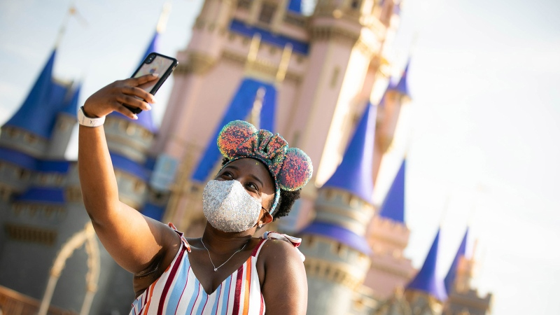 A guest stops to take a selfie at Magic Kingdom Park at Walt Disney World Resort on July 11, 2020, in Lake Buena Vista, Florida. (Walt Disney World Resort/Getty Images)