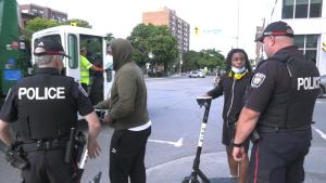 Ottawa police officers talk to two e-scooter riders in downtown Ottawa on Wednesday. (Shaun Vardon/CTV News Ottawa)