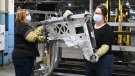 GM workers place vehicle truck fenders on a rack at the General Motors assembly plant during the COVID-19 pandemic in Oshawa, Ont., on Friday, March 19, 2021. THE CANADIAN PRESS/Nathan Denette