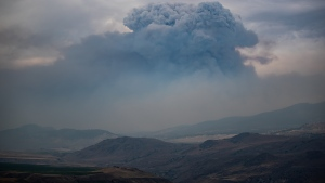 A pyrocumulus cloud, also known as a fire cloud, forms in the sky as the Tremont Creek wildfire burns on the mountains above Ashcroft, B.C., on Friday, July 16, 2021. (Darryl Dyck / THE CANADIAN PRESS)