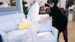 A customer drapes a chair with a plastic sheet before trying it out at a furniture store in St-Jean-sur-Richelieu, Que. on Monday, May 4, 2020. THE CANADIAN PRESS/Paul Chiasson