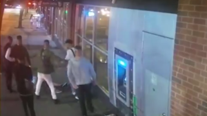 Men involved in an alleged assault are seen in a still image from security camera video as they surround a victim on the ground. (Video released by Vancouver police)