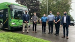From left: Kingston and the Islands MP Mark Garretson, Kingston city councillor Robert Kiley, Kingston transit services director Jeremy DaCosta, and mayor Bryan Paterson stand with transit operators as the city unveils its new fully electric buses. (Kimberley Johnson / CTV News Ottawa)