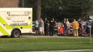 Emergency responders and members of the public attend to an injured person just south of Huron Street, near Sorel Road in London, Ont. on Thursday, July 29, 2021. (Jim Knight / CTV News)