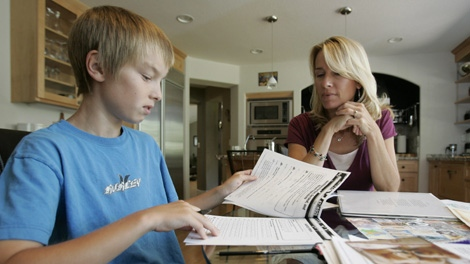 This photo taken July 1, 2009 shows Kerry Dickinson,right, with her son, Sam, 13, an eighth grader, doing math homework at their home in Danville, Calif. (AP Photo/Paul Sakuma)
