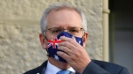 Australian Prime Minister Scott Morrison adjusts his mask during the announcement of a COVID-19 financial support package in Sydney, Tuesday, July 13, 2021. (Mick Tsikas/AAP Image via AP)