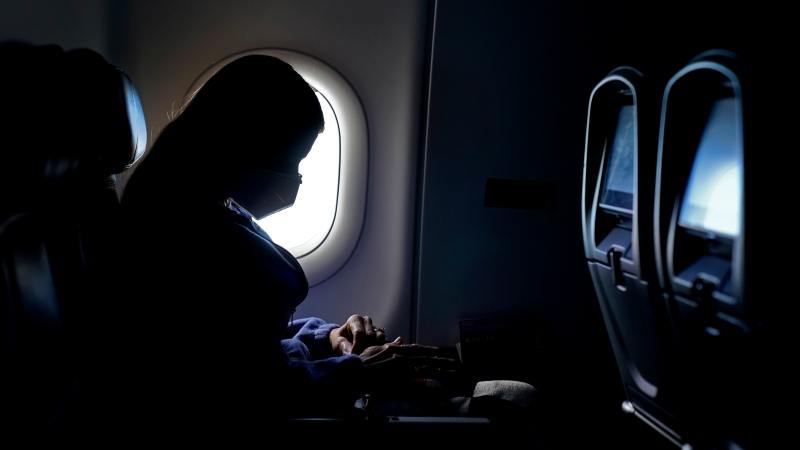 In this Feb. 3, 2021, file photo, a passenger wears a face mask she travels on a Delta Air Lines flight after taking off from Hartsfield-Jackson International Airport in Atlanta. (AP Photo/Charlie Riedel, File)
