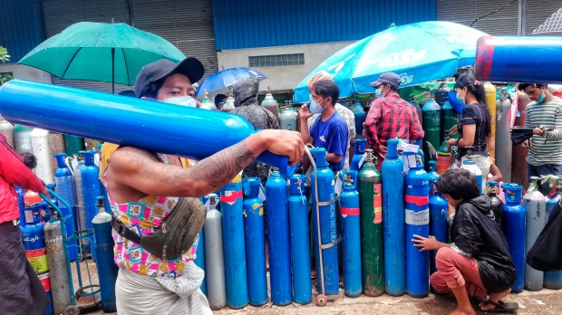 A man carries an oxygen tank as he walks past people waiting with oxygen tanks in need of refill outside the Naing oxygen factory at the South Dagon industrial zone in Yangon, Myanmar, Wednesday, July 28, 2021. (AP Photo)