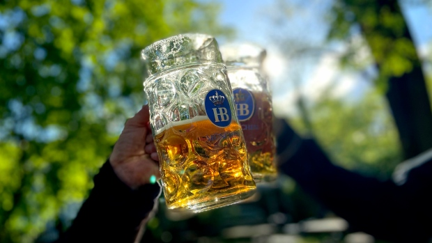 People toast with their beer mugs at the 'Taxisgarten' beer garden in Munich, Germany, Friday evening, May 15, 2021. (AP Photo/Matthias Schrader)