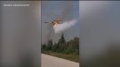 A screengrab of a video submitted by Sheldon Bayer shows a water bomber making a pass to fight a wildfire 50 kilometres south of The Pas. on Thursday, July 30, 2021.