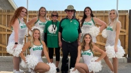 Jim Nedelcov and Mary Lynn Lovering, medal winners at the Harbour Landing Village Olympic Games, pose for a photo with the Saskatchewan Roughriders cheerleaders during the closing ceremonies on Friday. (Marc Smith/CTV News)