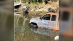 Photos shared with the post show a pickup truck with peeling orange paint submerged up to the top of its tires in the creek. (Facebook/BC Conservation Officer Service)