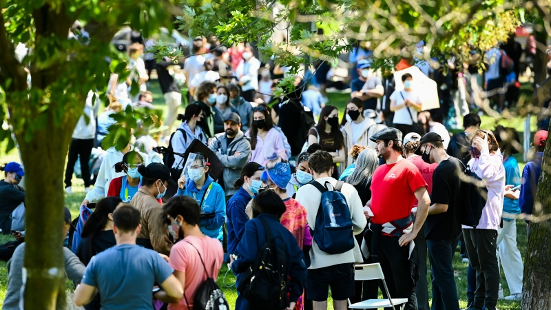 Thousands of people wait over six hours for their COVID-19 vaccine at a pop-up mass vaccination clinic at Jimmie Simpson Recreation Centre during the COVID-19 pandemic in Toronto on Thursday, June 17, 2021. THE CANADIAN PRESS/Nathan Denette