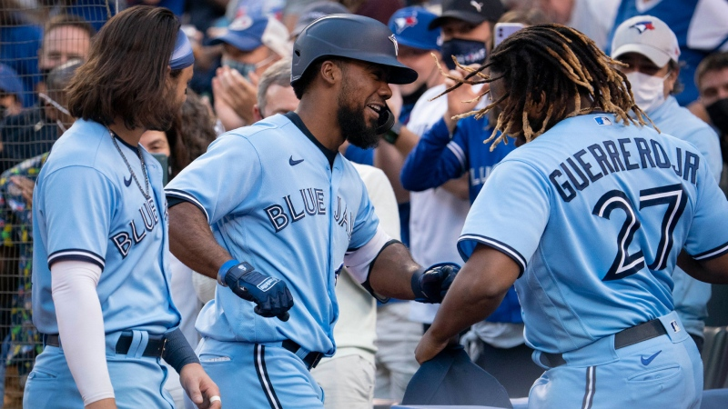 Toronto Blue Jays right fielder Teoscar Hernandez (37) celebrates with teammate Vladimir Guerrero Jr. (27) after hitting a solo home run against the Kansas City Royals during second inning MLB action in Toronto on Friday, July 30, 2021. THE CANADIAN PRESS/Peter Power