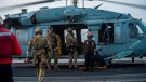 In this photo provided by the U.S. Navy, sailors assigned to an explosive ordnance unit board an MH-60S Seahawk helicopter on the flight deck of aircraft carrier USS Ronald Reagan to head to an oil tanker that was attacked off the coast of Oman in the Arabian Sea on Friday, July 30, 2021. Mass Communication Specialist 2nd Class Quinton A. Lee/U.S. Navy, via AP)