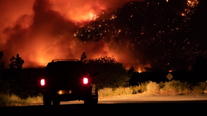 A motorist watches from a pullout on the Trans-Canada Highway as a wildfire burns on the side of a mountain in Lytton, B.C., Thursday, July 1, 2021. THE CANADIAN PRESS/Darryl Dyck