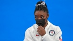 Simone Biles, of the United States, stands wearing a mask after she exited the team final with apparent injury, at the 2020 Summer Olympics, Tuesday, July 27, 2021, in Tokyo. (AP Photo/Natacha Pisarenko)
