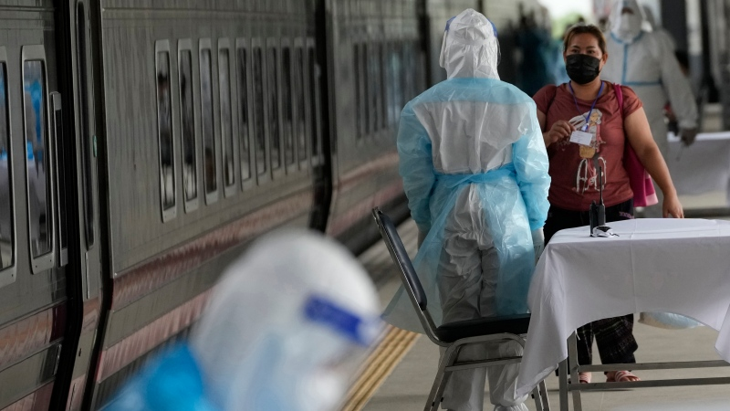 A health worker talks with a woman, who is among a group of people infected with COVID-19, as she arrived at Rangsit train station in Pathum Thani Province, Thailand, Tuesday, July 27, 2021. (AP Photo/Sakchai Lalit)
