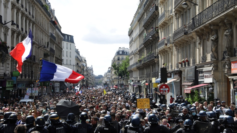 Protestors march waving French flags during a demonstration in Paris, France, Saturday, July 31, 2021. (AP Photo/Adrienne Surprenant)