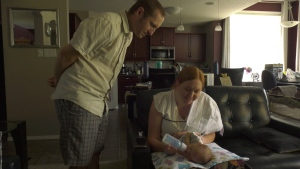 Marie and Taylor Schultz admiring their new baby boy. (Mackenzie Read/CTV News)
