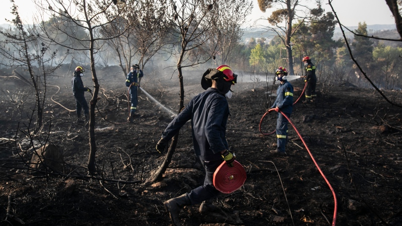 Firefighters spray water following a forest fire at Dionysos northern suburb of Athens, on Tuesday, July 27, 2021. Greek authorities have evacuated several areas north of Athens as a wildfire swept through a hillside forest and threatened homes despite a large operation mounted by firefighters. (AP Photo/Yorgos Karahalis)