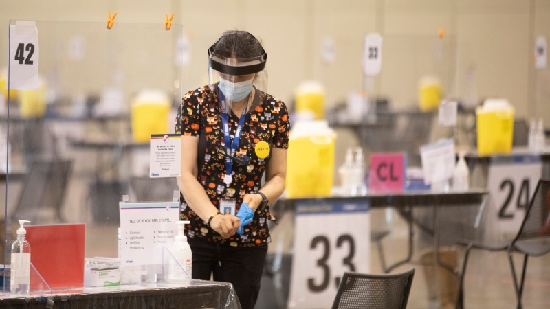 A health-care worker removes her protective gloves after sanitizing a workstation before doors open at a COVID-19 vaccine centre in Toronto on Friday, July 23, 2021. (THE CANADIAN PRESS / Chris Young)