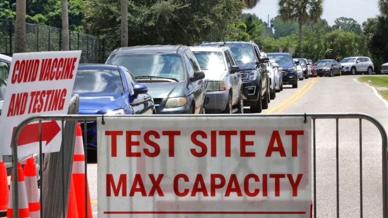Signage stands at the ready (foreground) in case COVID-19 testing at Barnett Park reaches capacity, as cars wait in line in Orlando, Fla., Thursday, July 29, 2021. (Joe Burbank/Orlando Sentinel via AP)