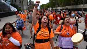 People march along Wellington Street during a rally to demand an independent investigation into Canada's crimes against Indigenous Peoples, including those at Indian Residential Schools, in Ottawa on Saturday, July 31, 2021. THE CANADIAN PRESS/Justin Tang