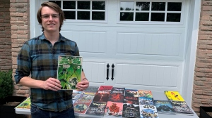 Max Chouinard standing with some of his comic book collection. (July 31, 2021)
