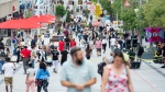 People walk along a street in Montreal, Saturday, July 31, 2021, as the COVID-19 pandemic continues in Canada and around the world. THE CANADIAN PRESS/Graham Hughes