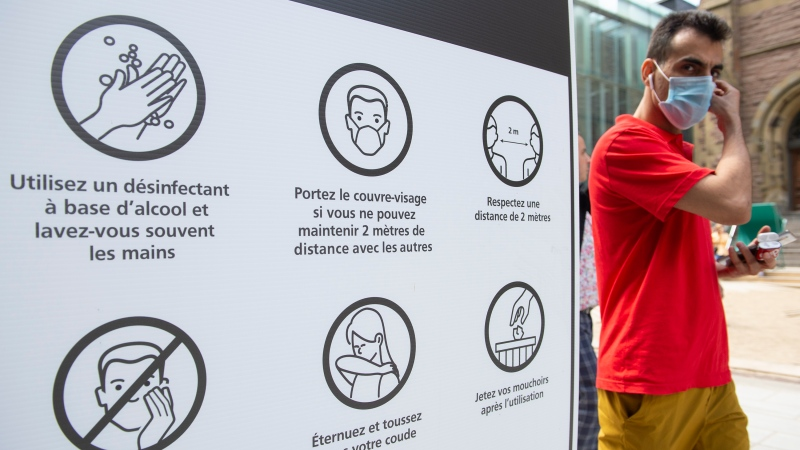 A man walks by a sign advising people of COVID-19 prevention measures in Montreal, Saturday, July 31, 2021. THE CANADIAN PRESS/Graham Hughes