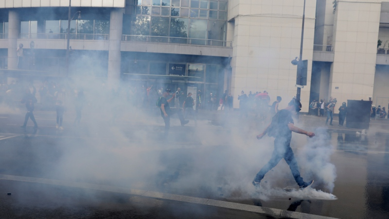 A protester kicks a gas canister during a demonstration in Paris, France, Saturday, July 31, 2021. Demonstrators gathered in several cities in France on Saturday to protest against the COVID-19 pass, which grants vaccinated individuals greater ease of access to venues. (AP Photo/Adrienne Surprenant)