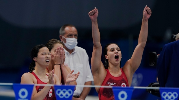 Canada's Maggie Mac Neil, left to right, Sydney Pickrem, Kylie Masse and Penny Oleksiak, in the water, react to their time to win a bronze medal in the women's 4 x 100m medley relay final during the Tokyo Summer Olympic Games, in Tokyo, Sunday, August 1, 2021. THE CANADIAN PRESS/Adrian Wyld