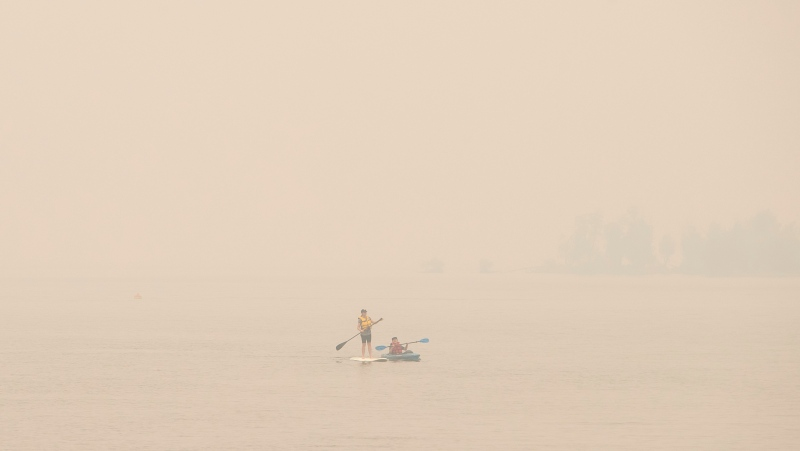 Wildfire smoke fills the air and obstructs the view of the mountains as people continue to take part in outdoor activities even though the air is 18 times above WHO exposure recommendation, in Sicamous B.C., on Thursday July 29, 2021. THE CANADIAN PRESS/Jason Franson