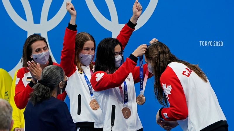 Canada's Kylie Masse and Sydney Pickrem cheer as Maggie Mac Neil gives Penny Oleksiak her bronze medal as they celebrate their finish in the women's 4 x 100m medley relay final during the Tokyo Summer Olympic Games, in Tokyo, Sunday, August 1, 2021. THE CANADIAN PRESS/Adrian Wyld